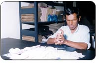 Photograph of a blind man making envelopes